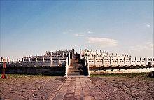 A fotografia da cor de uma estrutura de pedra de três níveis com grades em cada nível, visto de fora, de frente para uma escadaria que conduz ao nível superior.