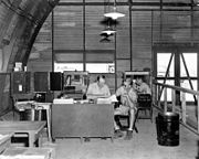 An office with desksm chairs and boxes inside a semi-cylindrical corrugated iron building.