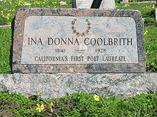 "A color photograph of a pink granite headstone amid lush green grass and yellow oxalis flowers. The headstone is engraved with a laurel wreath at the top, and reads ""Ina Donna Coolbrith"" 1841–1928 ""California's First Poet Laureate""."