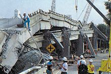 A collapsed elevated freeway with the upper deck resting on the lower deck and several pillars destroyed. Several people with hard hats are seen investigating the scene.