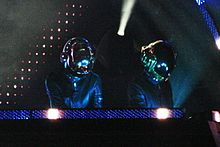 Two men wearing grey jumpsuits and robot helmets.