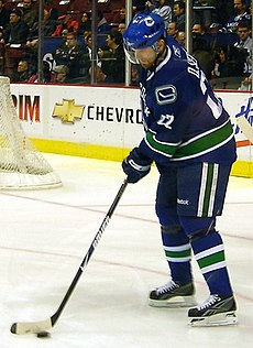 An ice hockey player wearing a blue jersey with green and white trim. Looking down, he his handling a puck on the ice with his stick.