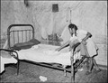 Daughter of Lawson Mayo, disabled miner, makes the bed in the four room house which the two adults and ten children... - NARA - 540970.tif