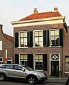 foto van Herenhuis met verdieping en omlopend schilddak. Eenvoudige lijstgevel, met versierd bovenlicht. Twee hardstenen stoeppalen met gietijzeren zijhekjes