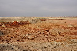 Landscape around the hot springs in Dallol; parts of the abandoned settlement are visible at horizon