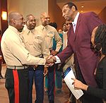 A tall African American man wearing purple suit is shaking hand with another African American man wearing a uniform, while three other men is watching on the background.