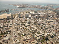 The East Village district of Long Beach, California, is in the right three-quarters of the foreground of this southwest-facing photo (the Alamitos Beach neighborhood makes up the left quarter of the foreground, on the east side of Alamitos Avenue, the diagonal street on the left). Downtown Long Beach is to the right. Queensway Bay/San Pedro Bay are visible, with the Queen Mary and part of the Port of Long Beach in the distance. Catalina Island is faintly visible on the horizon.