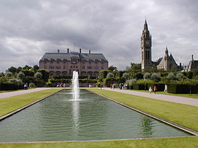 A rectangular lake with a central fountain, beyond which is the house, with the clock tower and chapel to its right