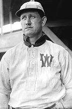 "A man, wearing a baseball cap and a white baseball uniform with the letter ""W"" on the left breast, faces forward towards the left."