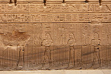 Relief showing four people with varying sets of hieroglyphs on their heads
