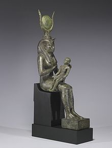 Smal statue of a seated woman, with a headdress of horns and a disk, holding an infant across her lap