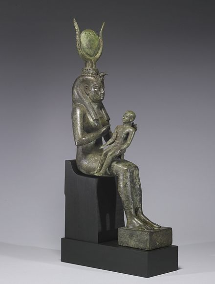 Small statue of a seated woman, with a headdress of horns and a disk, holding an infant across her lap