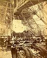 Eiffel Tower machinery with man beside wheel that raises elevator, during Paris Exposition.jpg