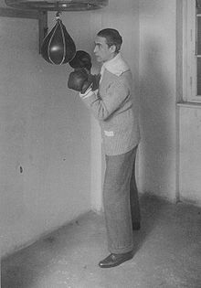 Deutsch posing with boxing gloves and a punching bag