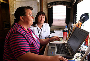 Adviser - A U.S. Federal Emergency Management Agency employee is shown how to log into the agency network by her supervisor