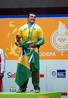 Brazilian athlete on the podium during the awards ceremony of the weightlifting competitions. Wearing the official uniform of the Brazilian delegation, he holds the flag of Brazil and a flowers bouquet. The bronze medal was hung around his neck.