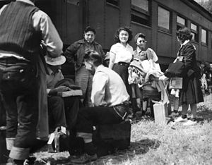 Granada War Relocation Center - Japanese American evacuees stand or sit with their suitcases and belongings in front of an Atchison, Topeka and Santa Fe Railway passenger car on August 30, 1942. The men and women wait for the bus ride to Camp Amache, Granada Relocation Center, southeastern Colorado. U.S. War Relocation Authority photo