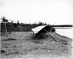Fish drying rack and overturned boat for shelter on the shore of the Kuzitrin River, ca 1904 (NOWELL 192).jpeg