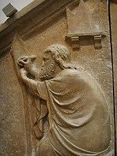 Reliéf proti zdi ukazuje, že vousatý muž se natáhl rukama, zatímco jeho šaty jsou přehozené přes jeho tělo.