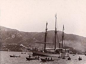 Un trois-mâts, propulsé à la vapeur, avance dans un bras de mer entouré de nombreuses barques à rame. À l'arrière-plan se profile une ligne de collines, avec quelques immeubles faiblement visibles au bord de l'eau.