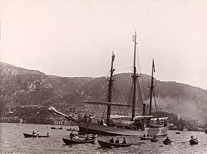 A three-masted ship, under steam power, moves across a stretch of water attended by several rowing boats. In the background is a line of hills, with buildings faintly visible at the water's edge.