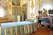 Photo d'une pièce avec un parquet en bois, une cheminée, de grands miroirs, des peintures et des boiseries dorées