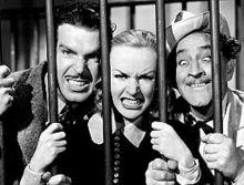 Фред МакМюррей, Кэрол Ломбард и Бэрримор корчили рожи за решеткой;  МакМюррей и Ломбард свирепо показывают зубы, а Бэрримор тупо скрещивает глаза.