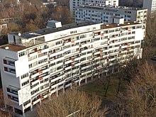 Walter-Gropius-Haus: Beitrag zur Internationalen Bauausstellung 1957 – ein Zeilenbau mit charakteristischem Grundriss in Kreissegmentform und plastischer Fassade.