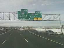 A sign in a snowy area indicating an exit for I-270 to Fort Collins and SH 35 as the next exit