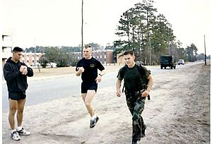 Radio Reconnaissance Platoon - A Sergeant (center) encourages an RRP candidate (right) during the last few yards of the Ruck Run event of the Indoc.