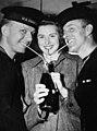 Ingrid Bergman with servicemen drinking soda during WWII (23221556673).jpg
