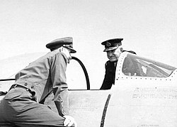 Two men in military uniforms with peaked caps on opposite sides of a military aircraft cockpit with open canopy