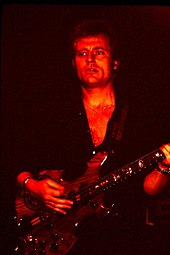 A red tinged photograph of John Paul Jones playing a bass guitar