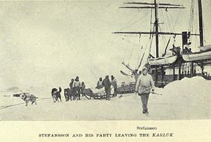 In the foreground a white-clad figure strides towards the camera. Behind him a group of men and dogs stand around a loaded sledge. To the right can be seen the upper parts of a ship, with heavy snow piled up at its sides.