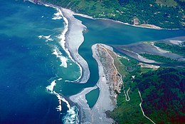 Aerial view of the river flowing between peninsulas of sand and into the ocean, which is the same color as the river water