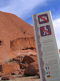 Tall sign with no entry and no photos symbols, in front of the base of a tall red rock