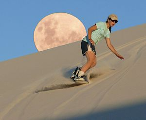 Sandboarding - Woman sandboarding at Atlantis Dunes in South Africa.