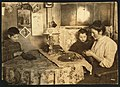 Late at night. Sewing tapes on gloves. The boy helps. Family of five sleep in room where the work is done. LOC cph.3a26906.jpg