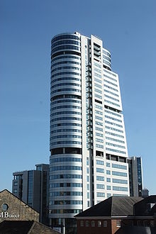 A tall modern building of 32 floors. On the left of the services shaft, all the floors of the tower are semicircular, as are the top four floors to the right. Below the latter, the remaining floors diminish in size from top to bottom and their right sides form a slope.
