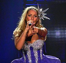 A blonde woman with a star head piece singing into a microphone