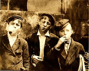 Tobacco smoking - Newsies smoking at Skeeter's Branch, St. Louis, MO. Photograph by Lewis Hine, 1910
