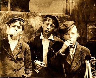 Tobacco smoking - Newsies smoking at Skeeter's Branch, St. Louis, MO. Photograph by Lewis Hine, 1910