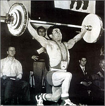 A man completing his weightlifting routine wearing one-piece costume and weightlifting shoes