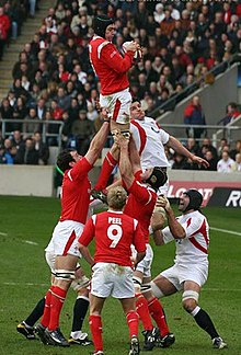 A Welsh player grasping the ball while being held in the air by his teammates following a line-out