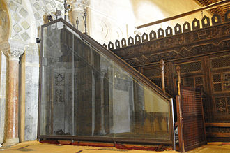 Minbar - The minbar of the Great Mosque of Kairouan (Mosque of Uqba); this pulpit, the oldest in existence, is still in its place of origin (in the prayer hall of the mosque) and it is protected by a glass panel in order to preserve this precious preaching chair, in Kairouan, Tunisia.
