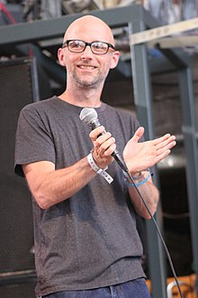 Moby holding a microphone and clapping