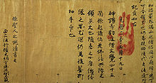 Texts in Chinese letters on brownish aged paper. A red handprint is placed over the text.