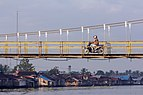 Motorcyclist crossing the Martapura River, South Kalimantan, 2018-07-28 02.jpg