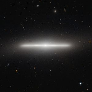Galactic plane - Galaxy NGC 4452 is being viewed edge-on from Earth, showing its galactic plane with the nucleus at center.