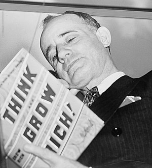 Napoleon Hill - Napoleon Hill holding his book Think and Grow Rich, 1937.